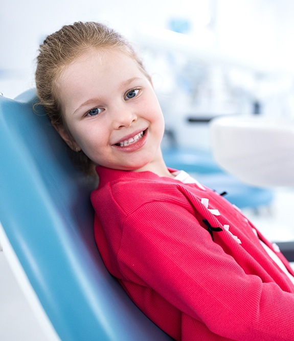 Smiling young girl in dental office for children's dentistry appointment