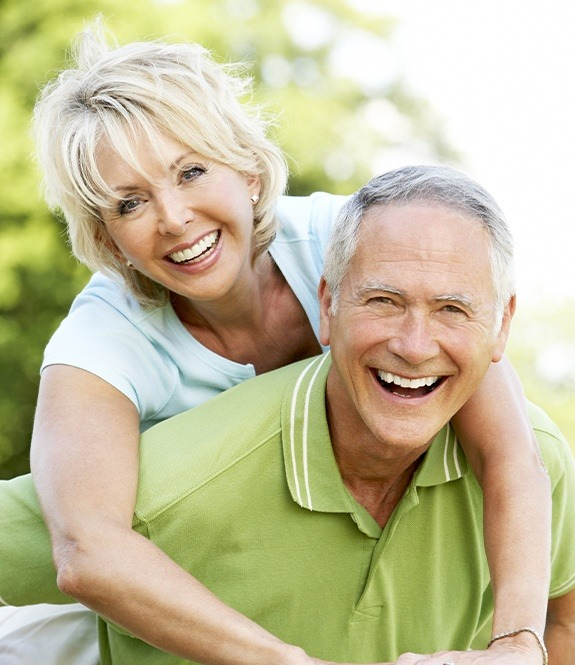 Older man and woman with dentures smiling together outdoors