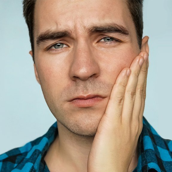 Frowning man holding cheek before emergency dental care