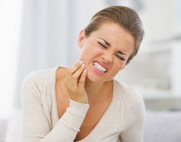 Woman with toothache holding cheek