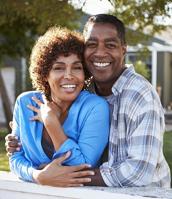 Smiling man and woman with dental insurance