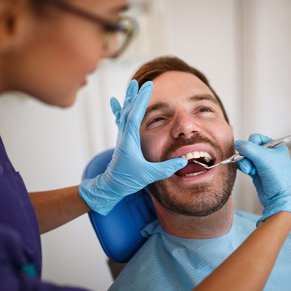 Man receiving dental checkup covered by dental insurance plan