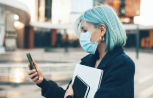 person calling their dentist in Lancaster to schedule an appointment while wearing a mask