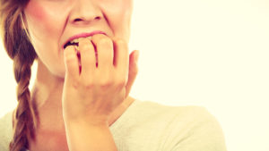 woman biting nails from dental anxiety