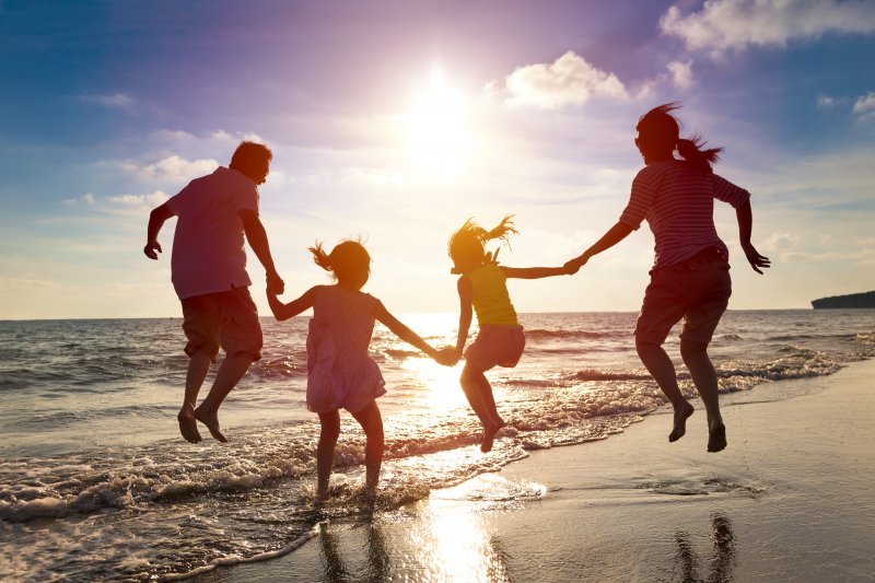 family jumping together on the beach during summer vacation